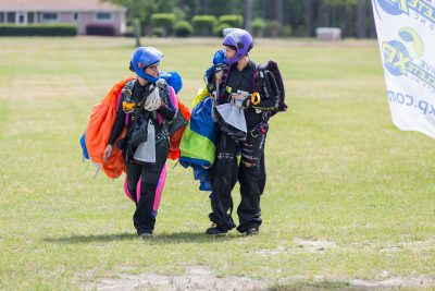 Skydivers walking in together from the landing area
